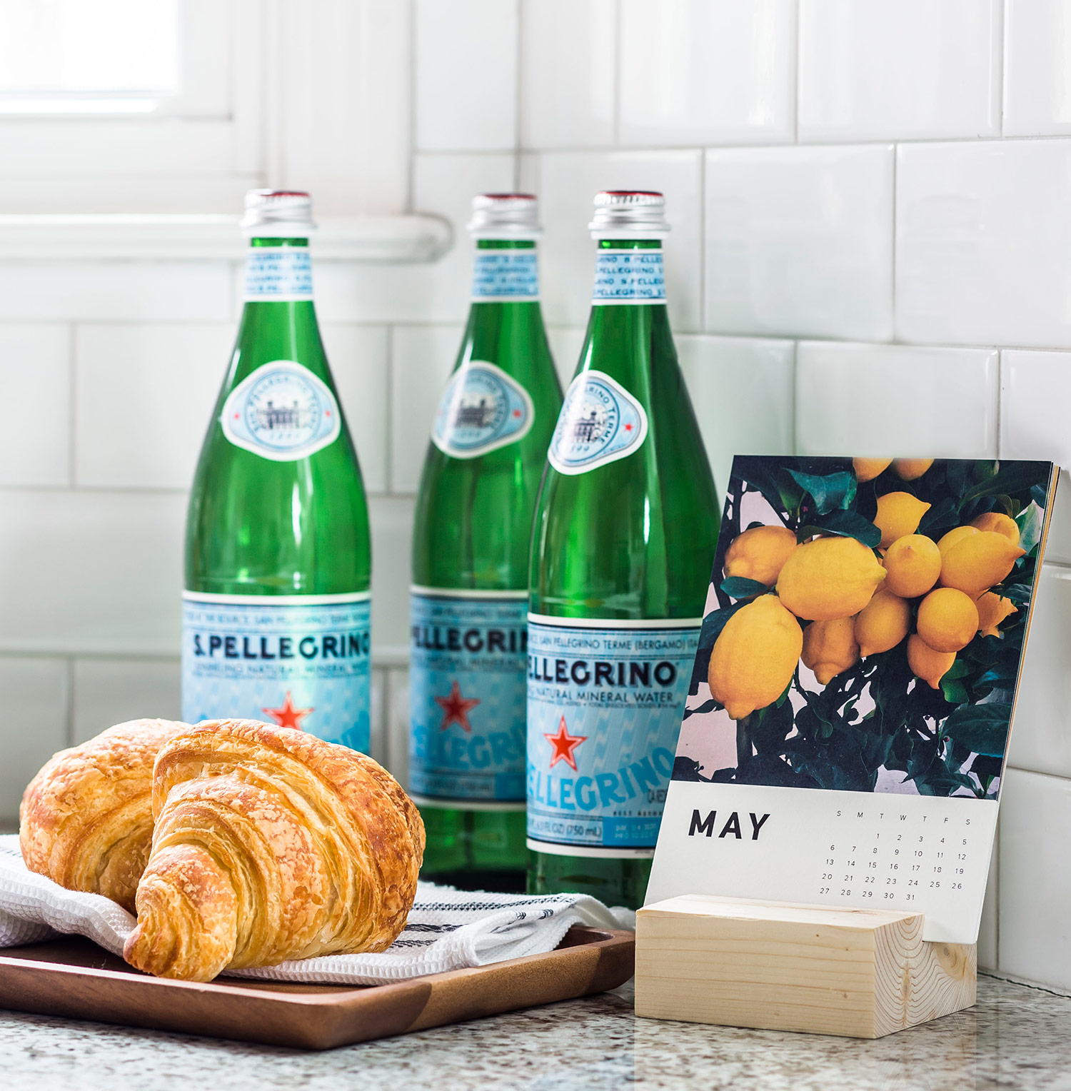 Croissant and sparkling water sitting on a kitchen counter next to calendar