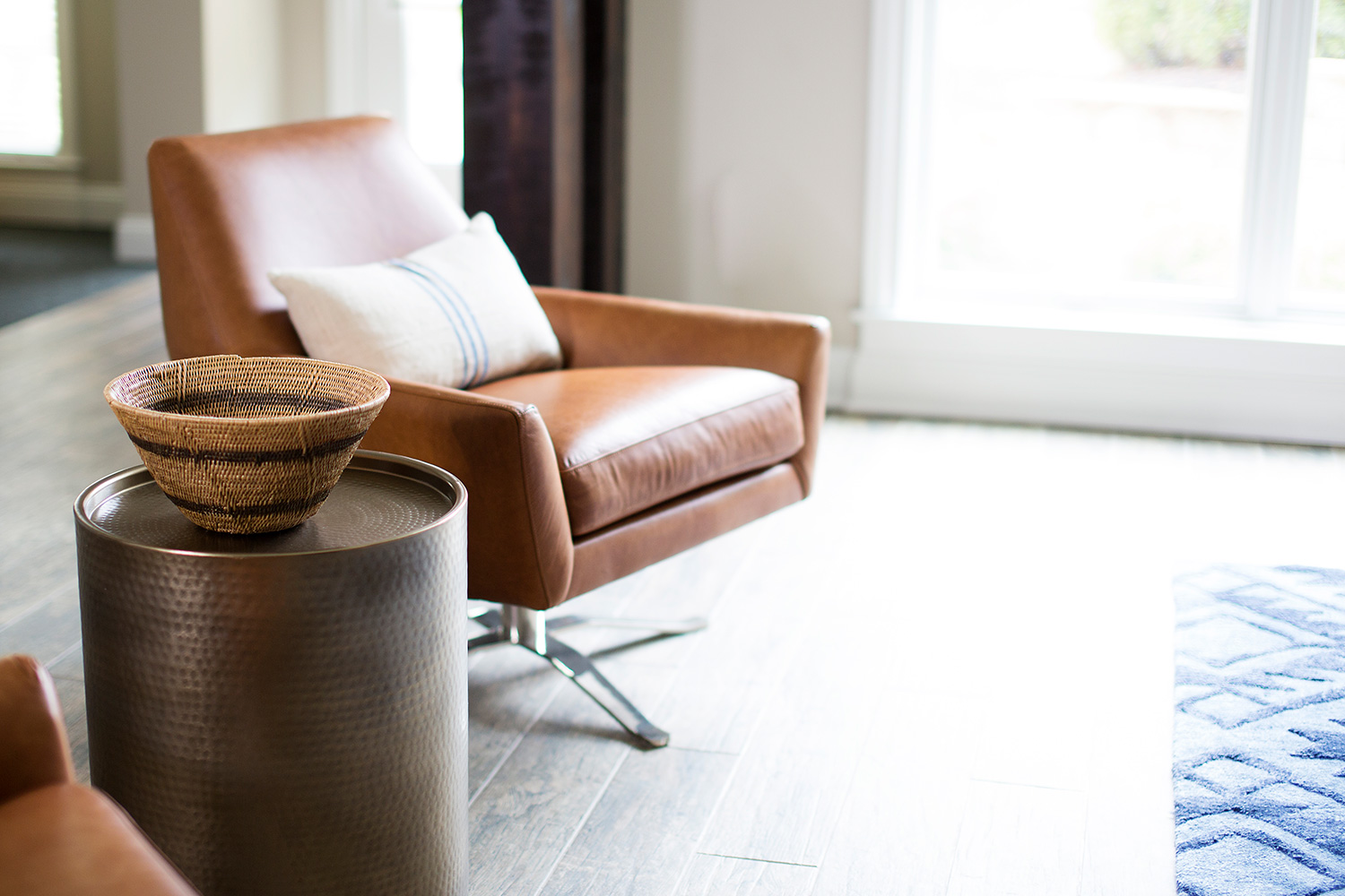 Leather swivel chair and hammered side table in basement