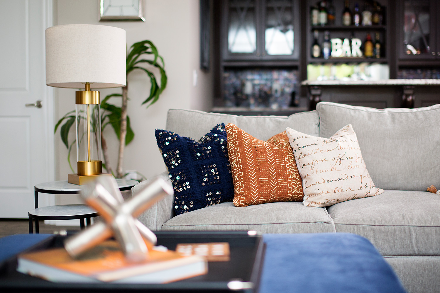 Casual basement with grey sofa and navy ottoman