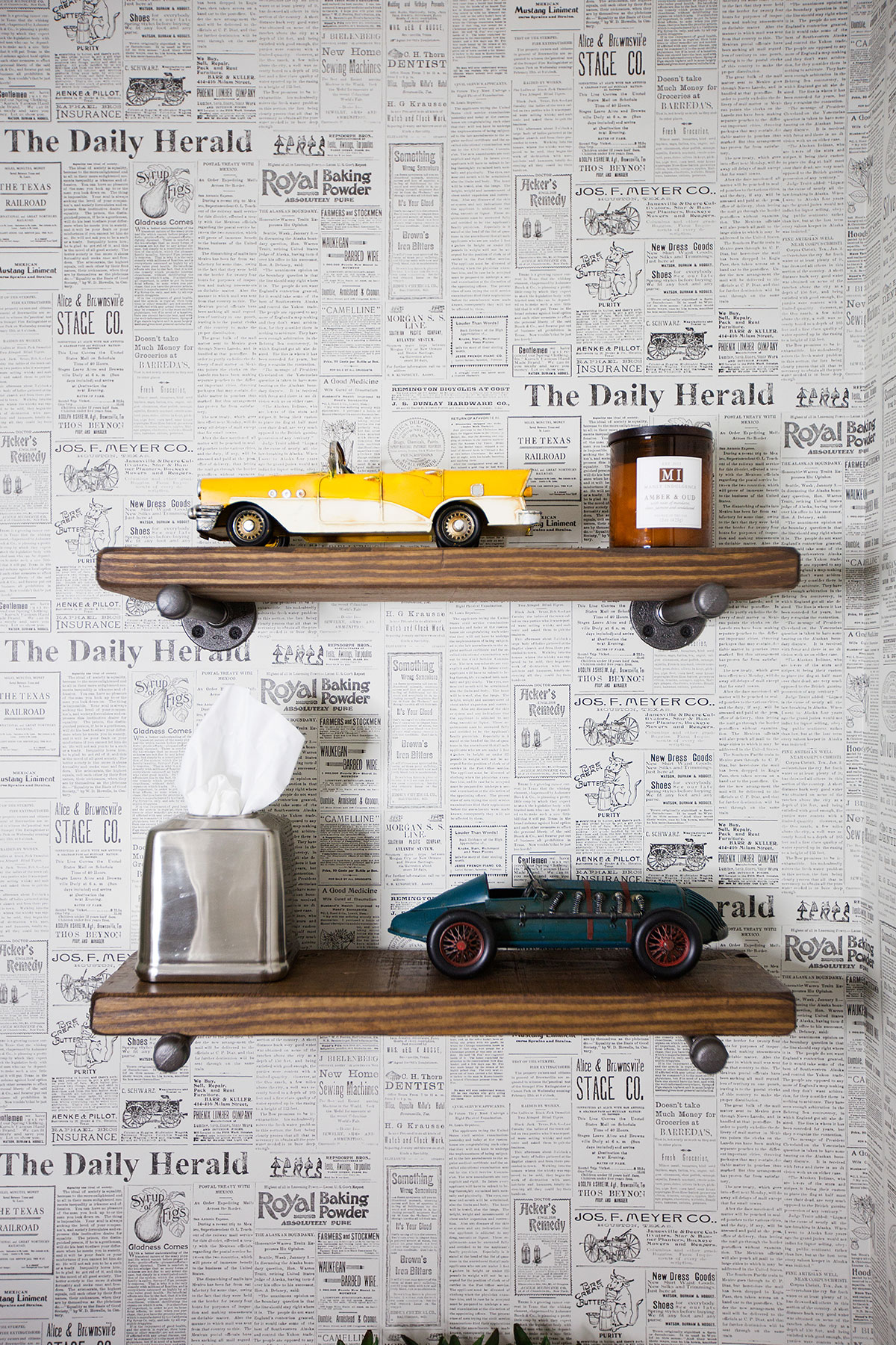 Powder room with newsprint wallpaper wood ledges and model cars