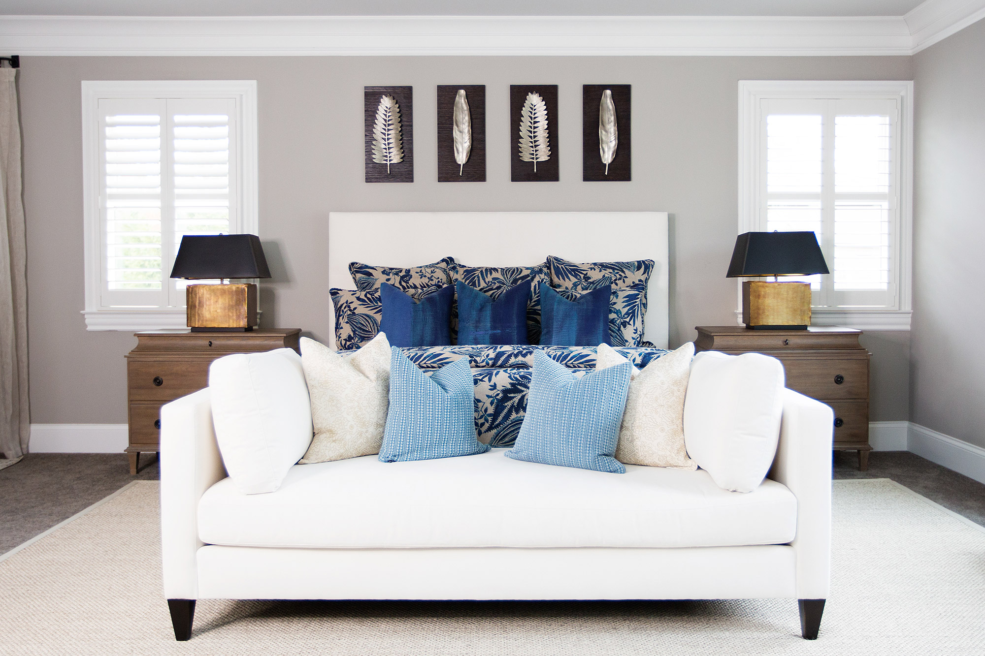 Transitional master bedroom with white upholstered bed frame and chaise at foot of bed