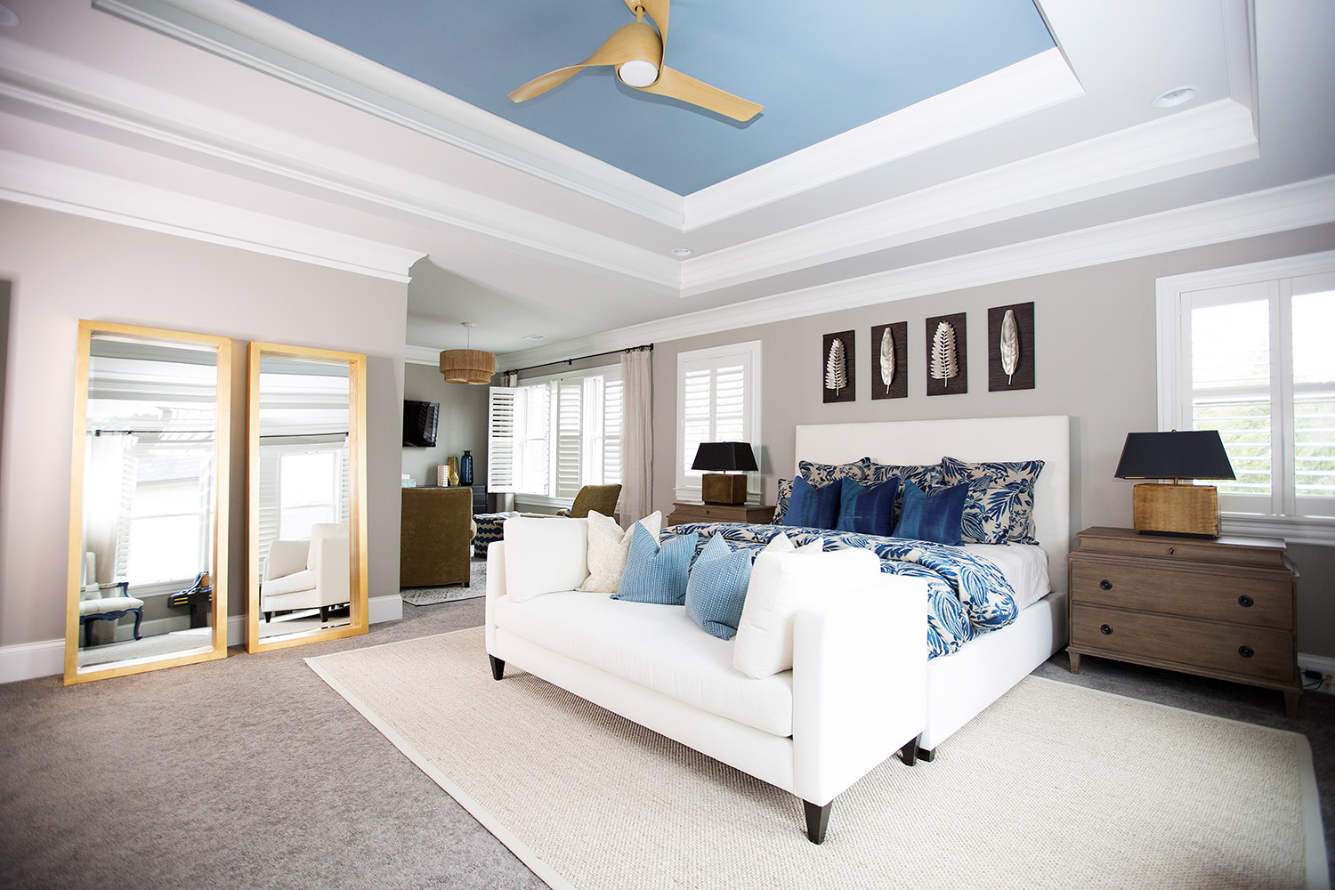 Transitional master bedroom with white upholstered bed frame, leaning mirrors, and chaise at foot of bed