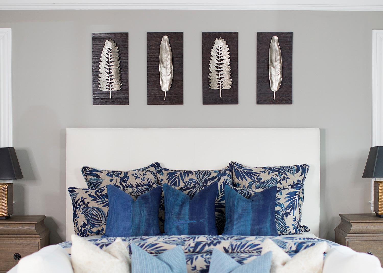 Leaf art above upholstered bed frame in transitional master bedroom