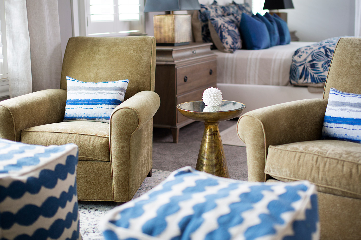 Upholstered chairs in sitting area in transitional master bedroom