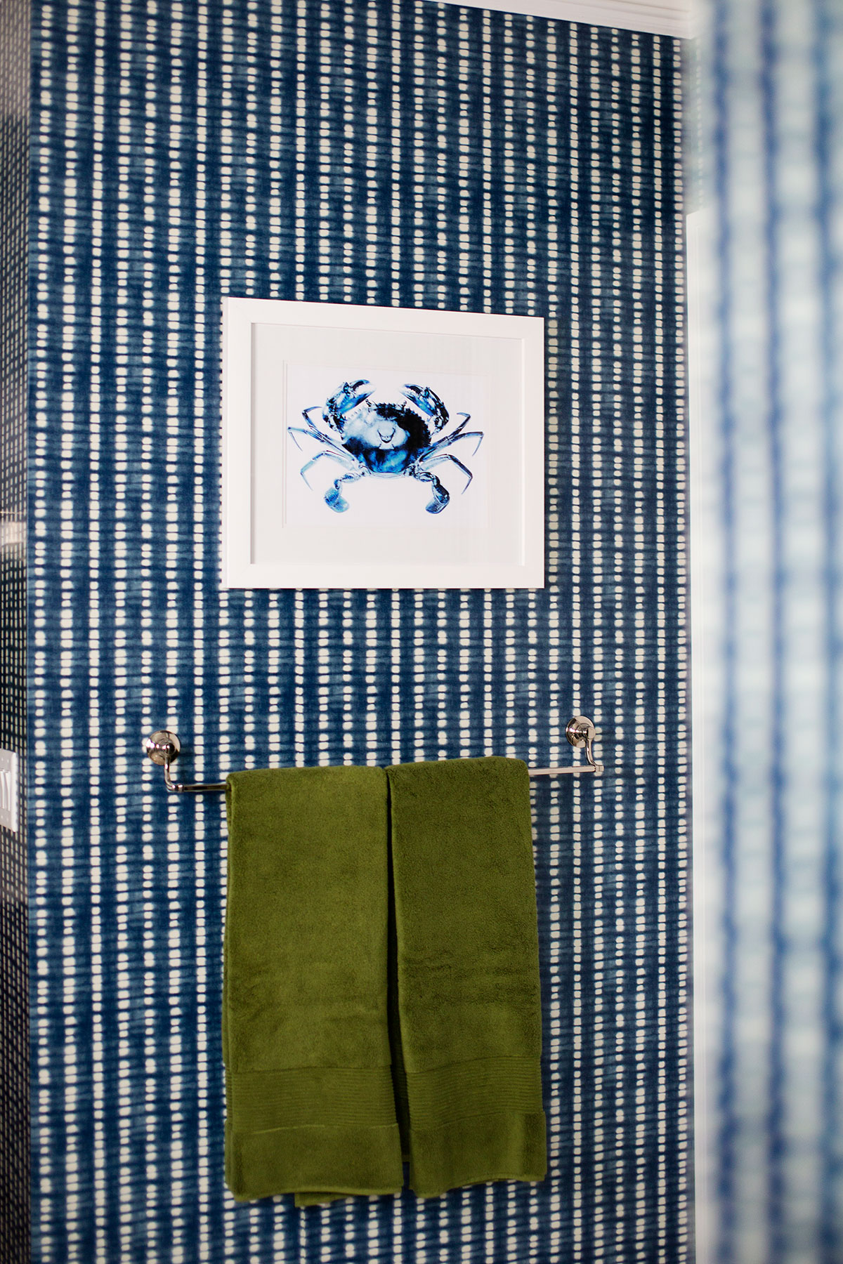 Blue and white wallpaper with crab artwork in transitional master bathroom