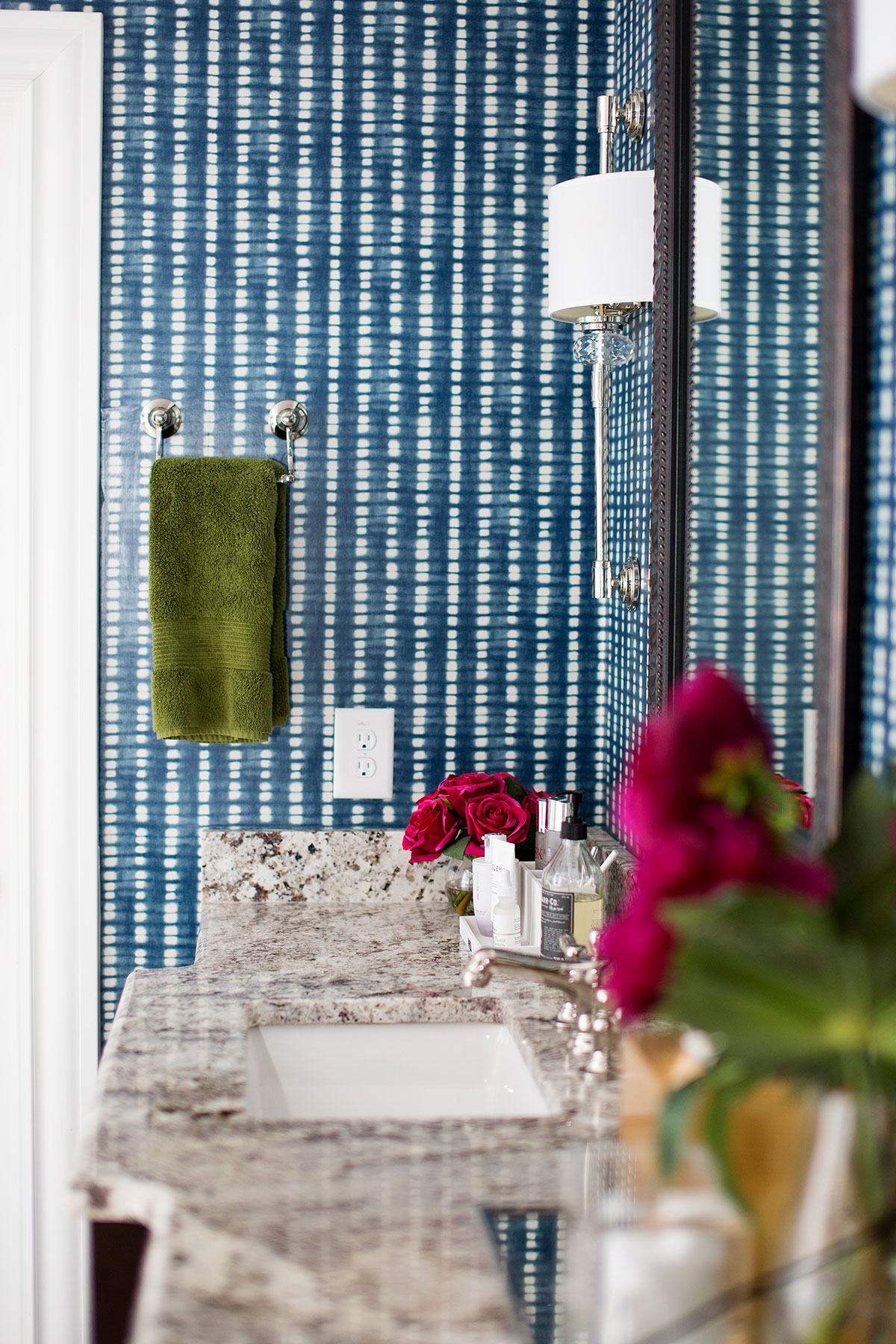 Built in vanity in master bathroom with blue and white wallpaper