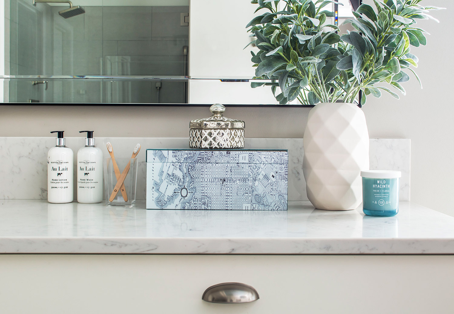 Custom built-in vanity with marble countertop and white cabinetry in master bathroom