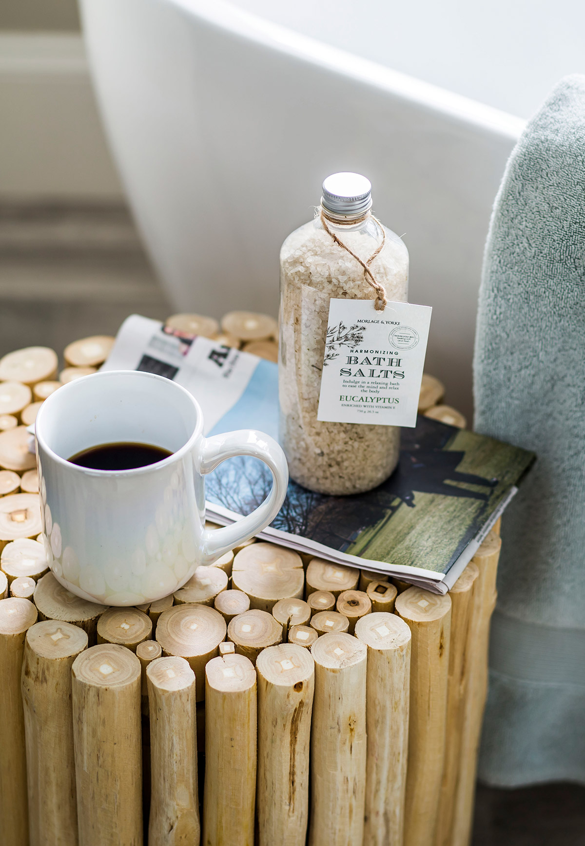 Wood stool in master bathroom with bath salts, a magazine, and a cup of coffee