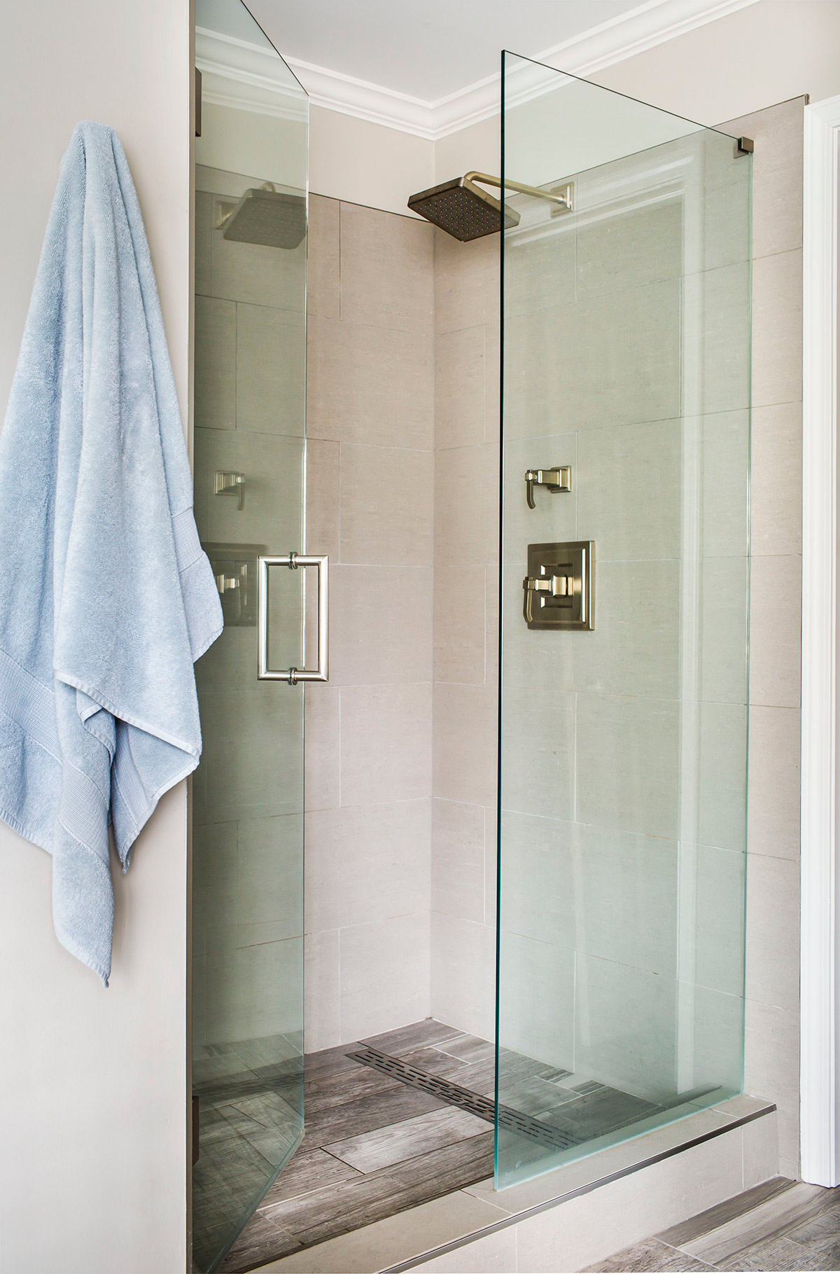 Walk-in shower with frameless glass door, wood look tile, and linear drain