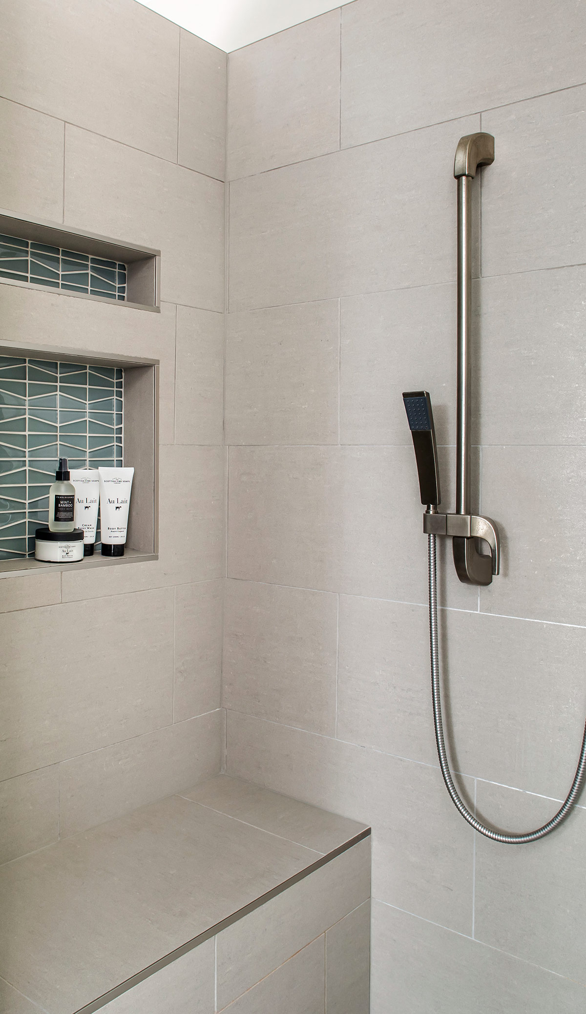 Master bathroom shower with grey tiles, bench, niche, and handheld shower head