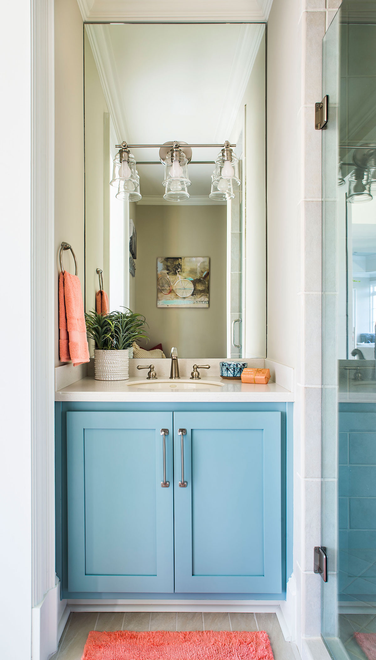 Colorful, coastal bathroom with turquoise cabinetry and brushed nickel hardware