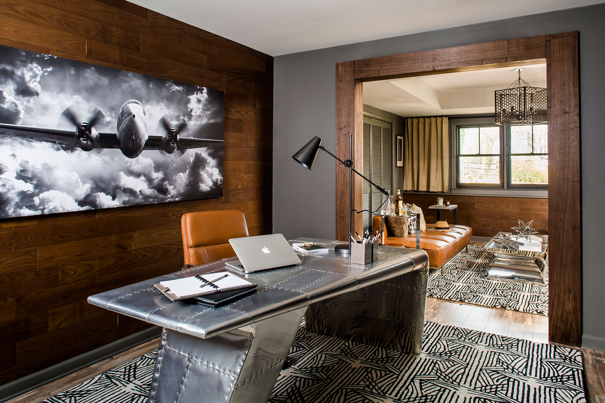 Masculine basement office with wood paneling, industrial desk, and leather accents.