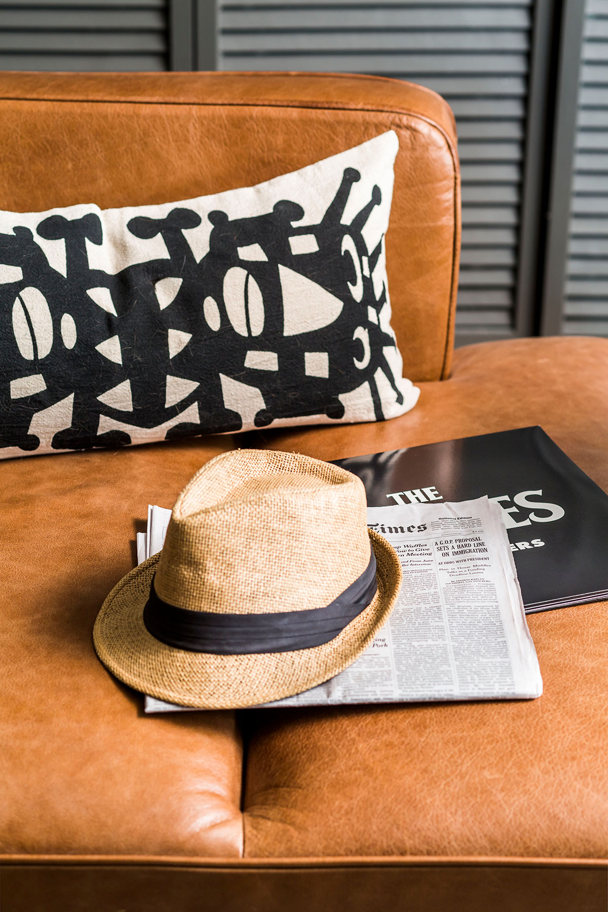 Leather chaise with black and white throw pillow, newspaper, and hat