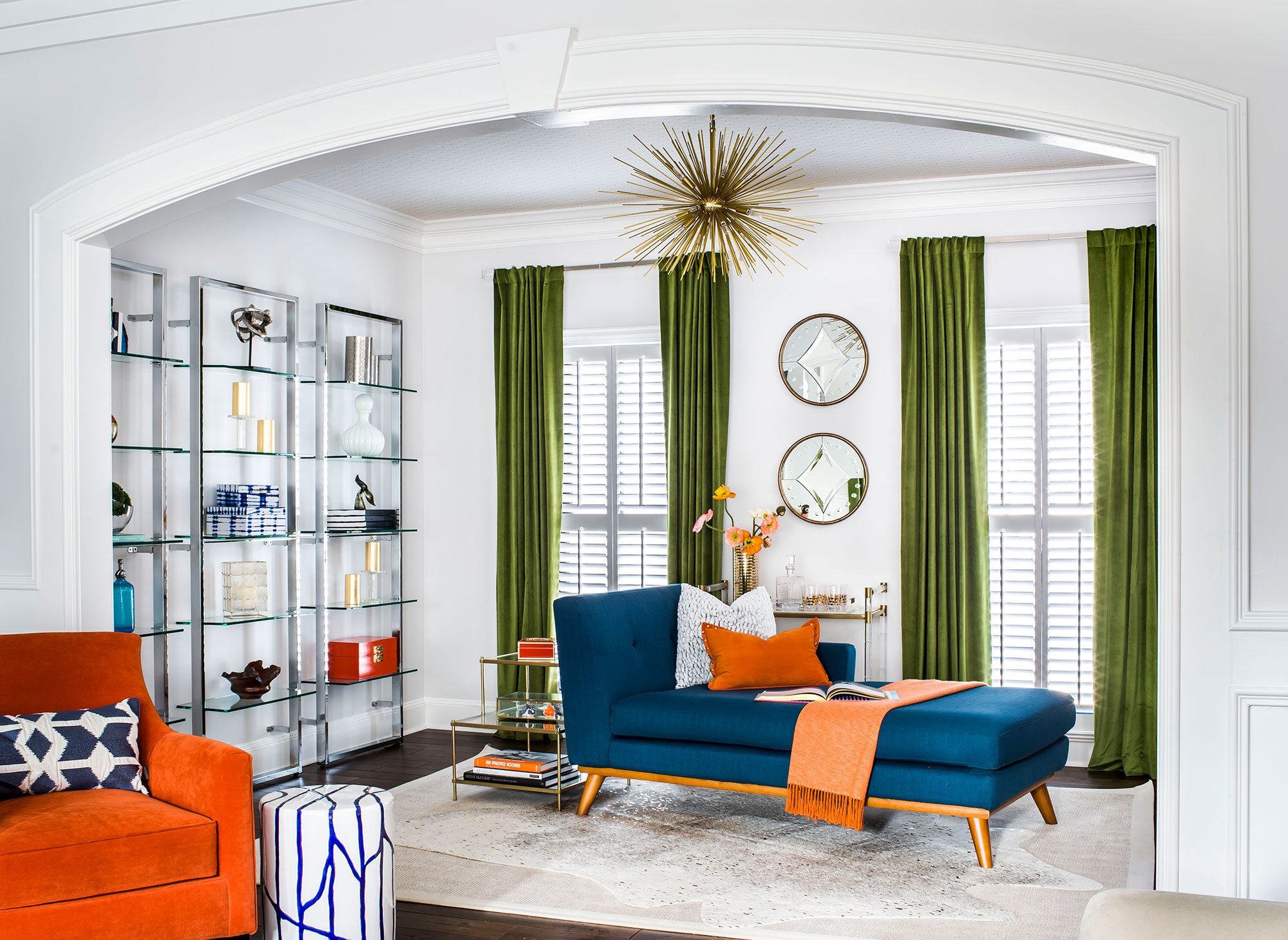 Contemporary sitting room with glass storage, green velvet curtains, and blue midcentury modern chaise