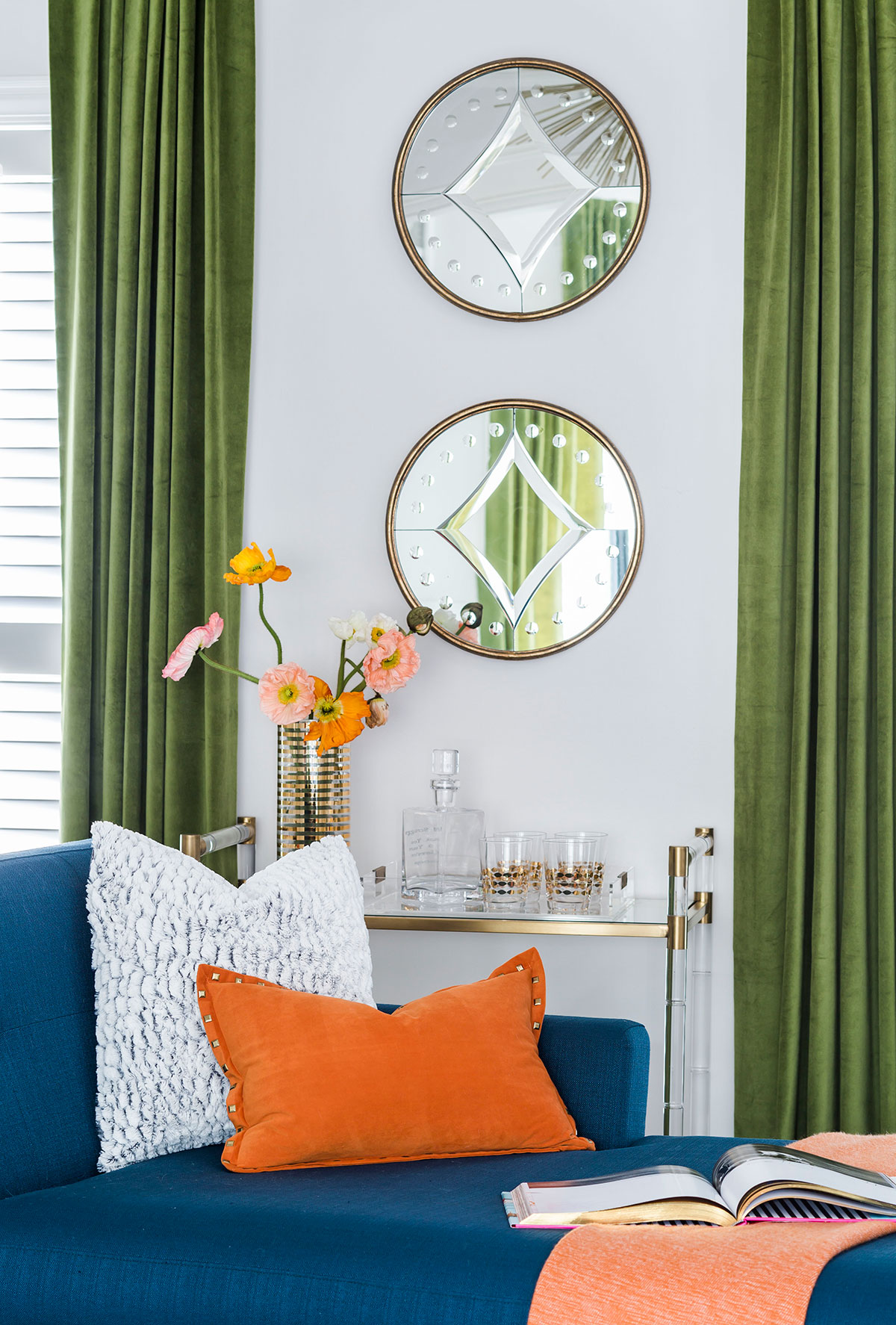 Round mirrors above bar cart in sitting room