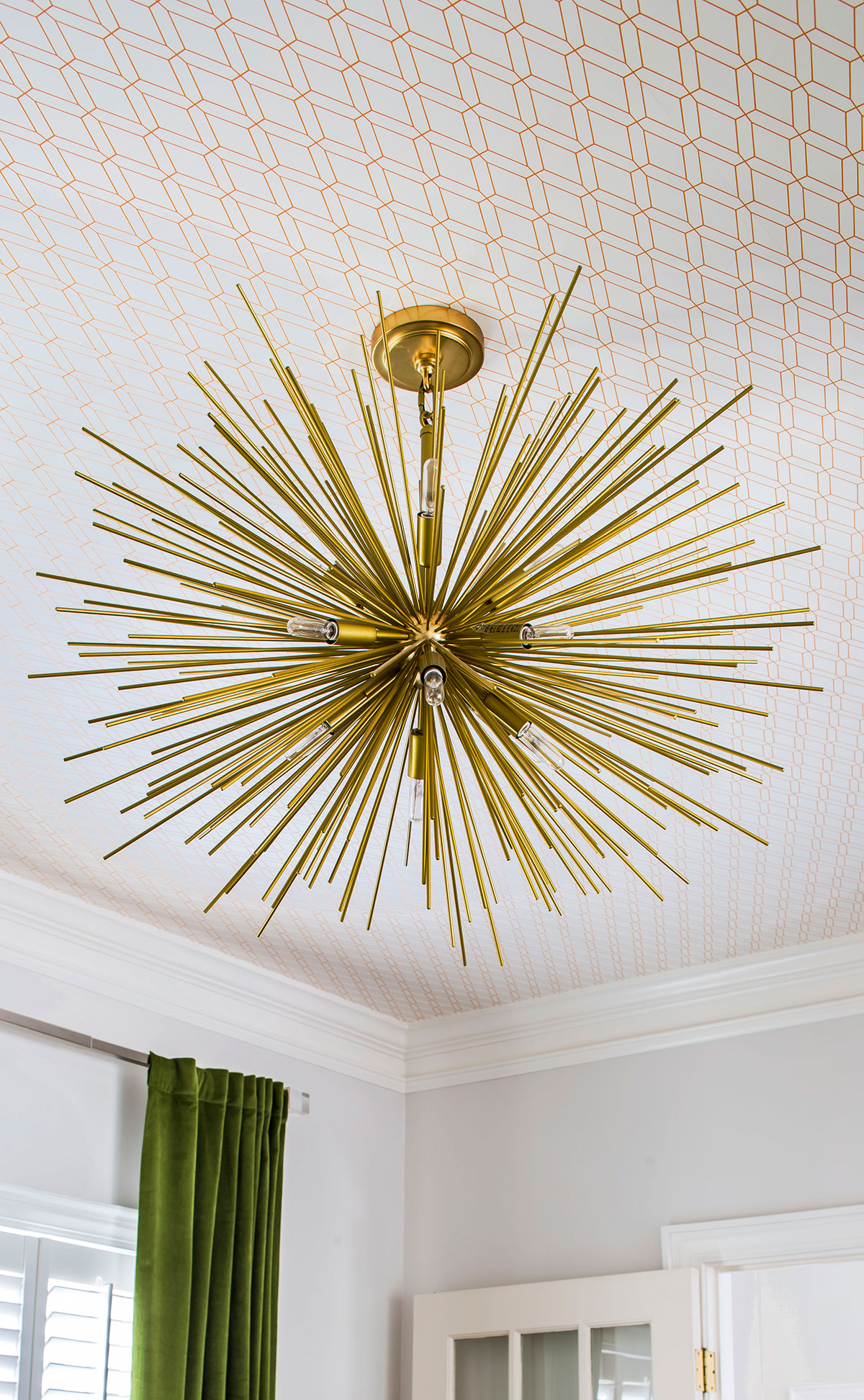 Wallpapered ceiling with brass midcentury modern chandelier
