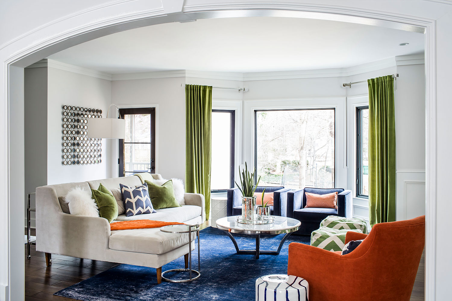 Living room with navy area rug, beige sectional and a mix of midcentury modern and contemporary styling