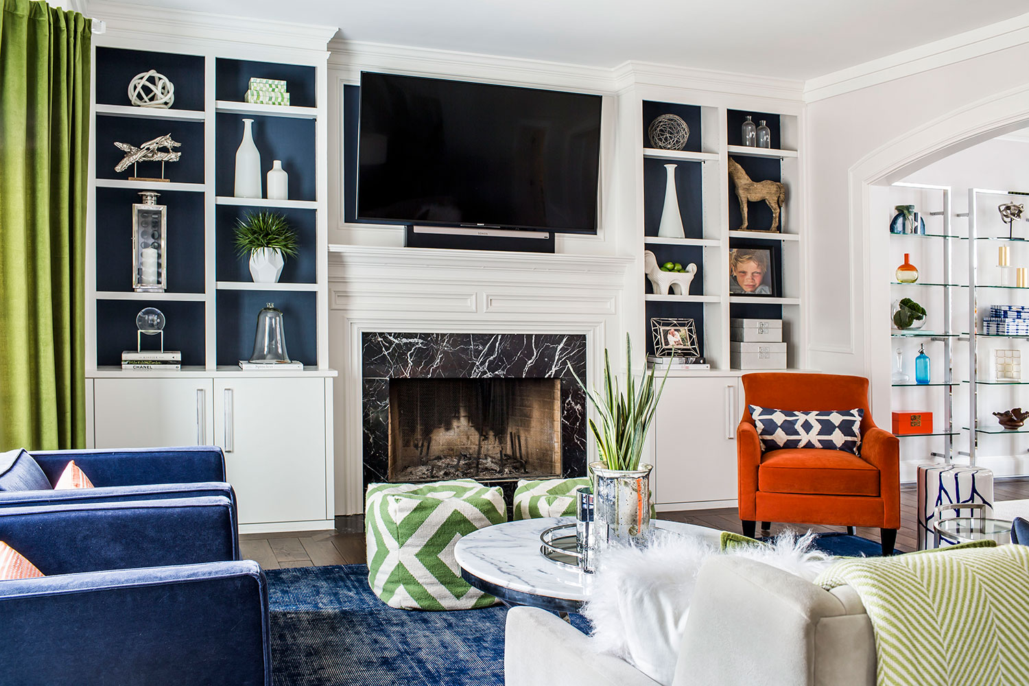 Living room with navy area rug, orange chair and a mix of midcentury modern and contemporary styling