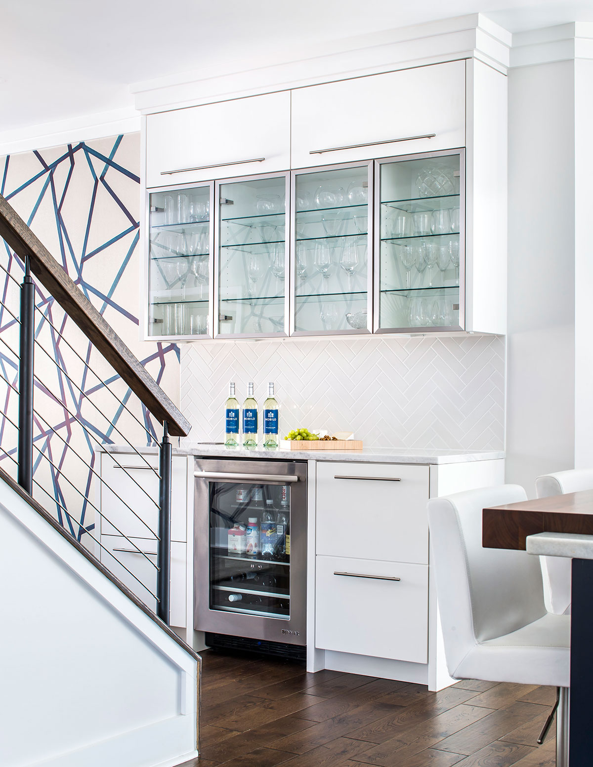 White built-in cabinetry with clear glass doors for storage of glassware