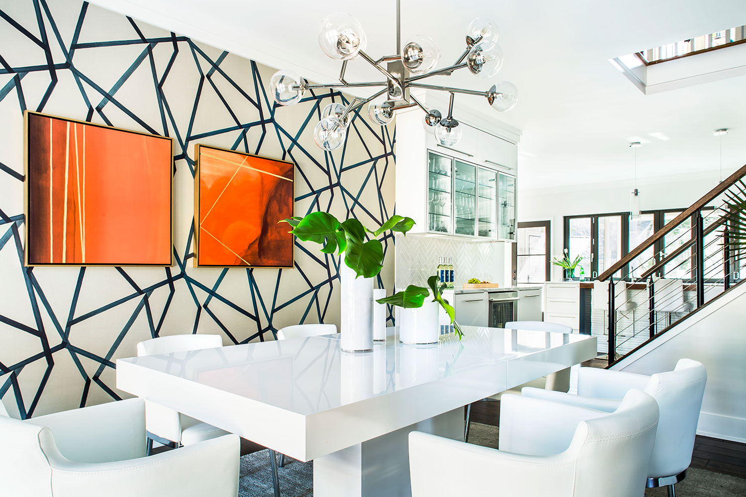 Contemporary dining room with geometric wallpaper, white furniture, and polished nickel chandelier