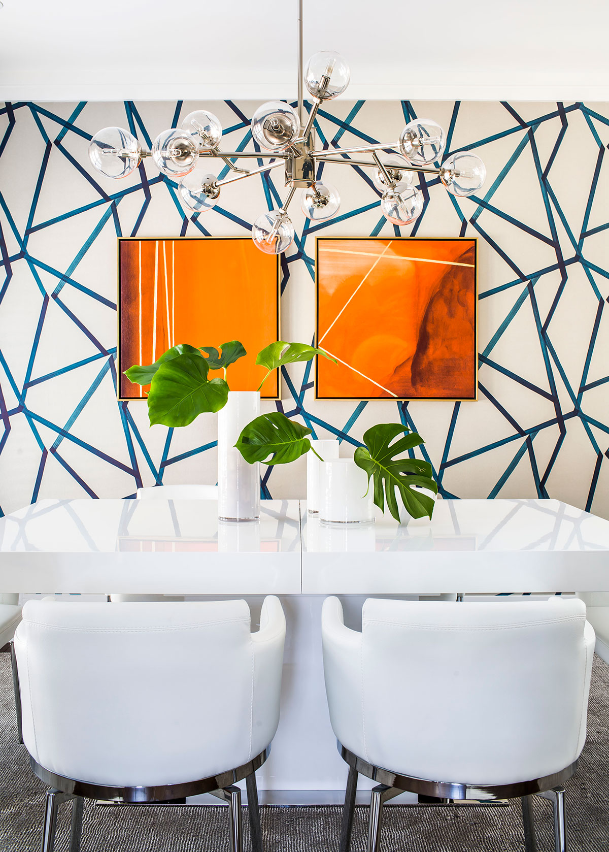 Contemporary dining room with white furniture and geometric wallpapered wall
