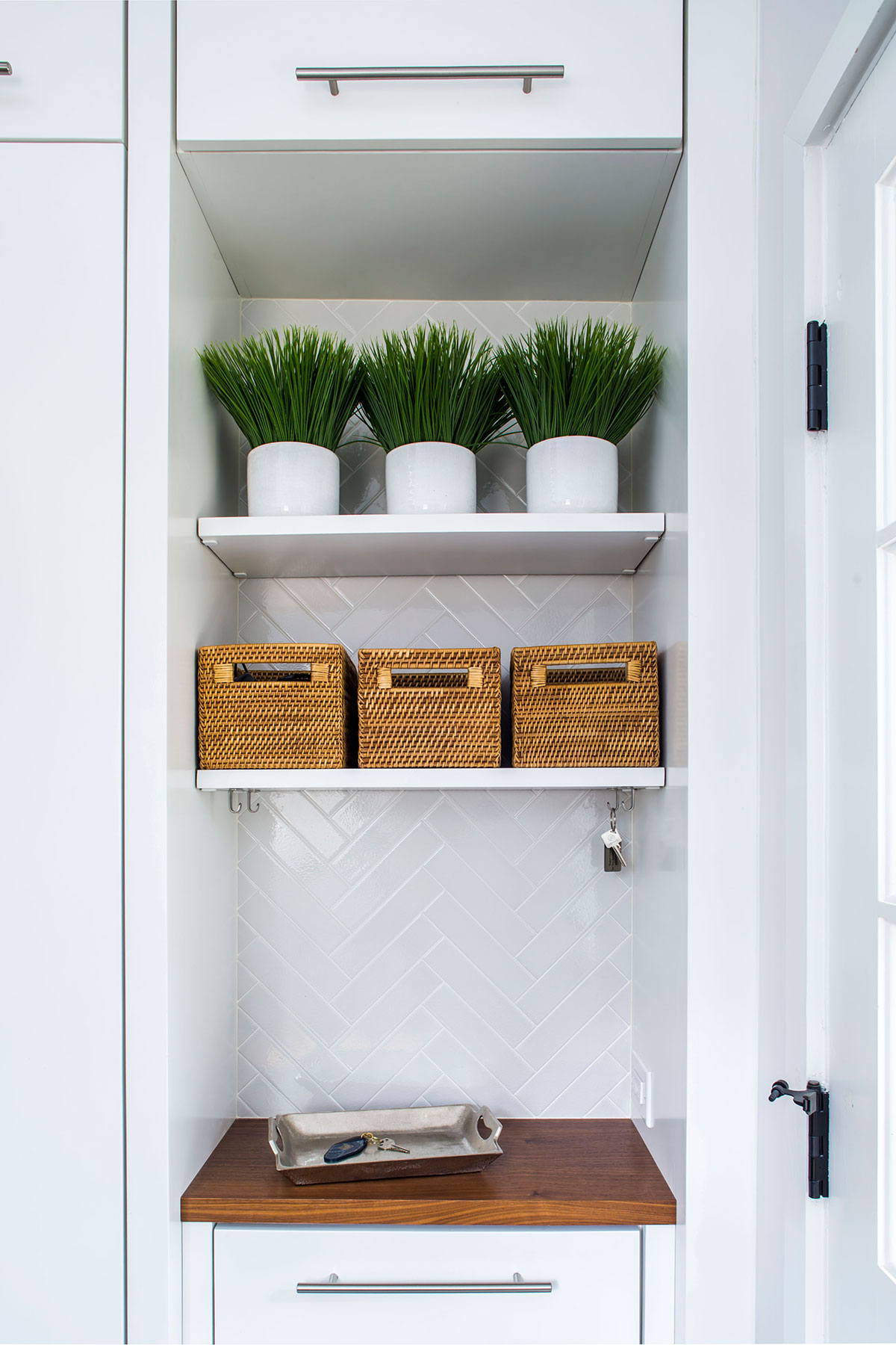 Contemporary mudroom shelving with wood countertop and white tile backsplash