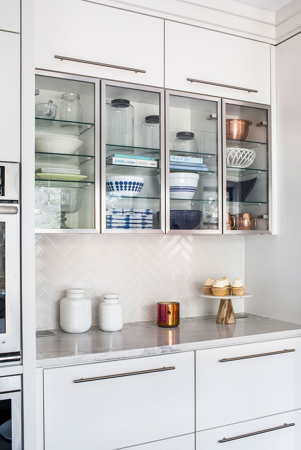 Contemporary kitchen with white backsplash, marble countertops, and glass shelving