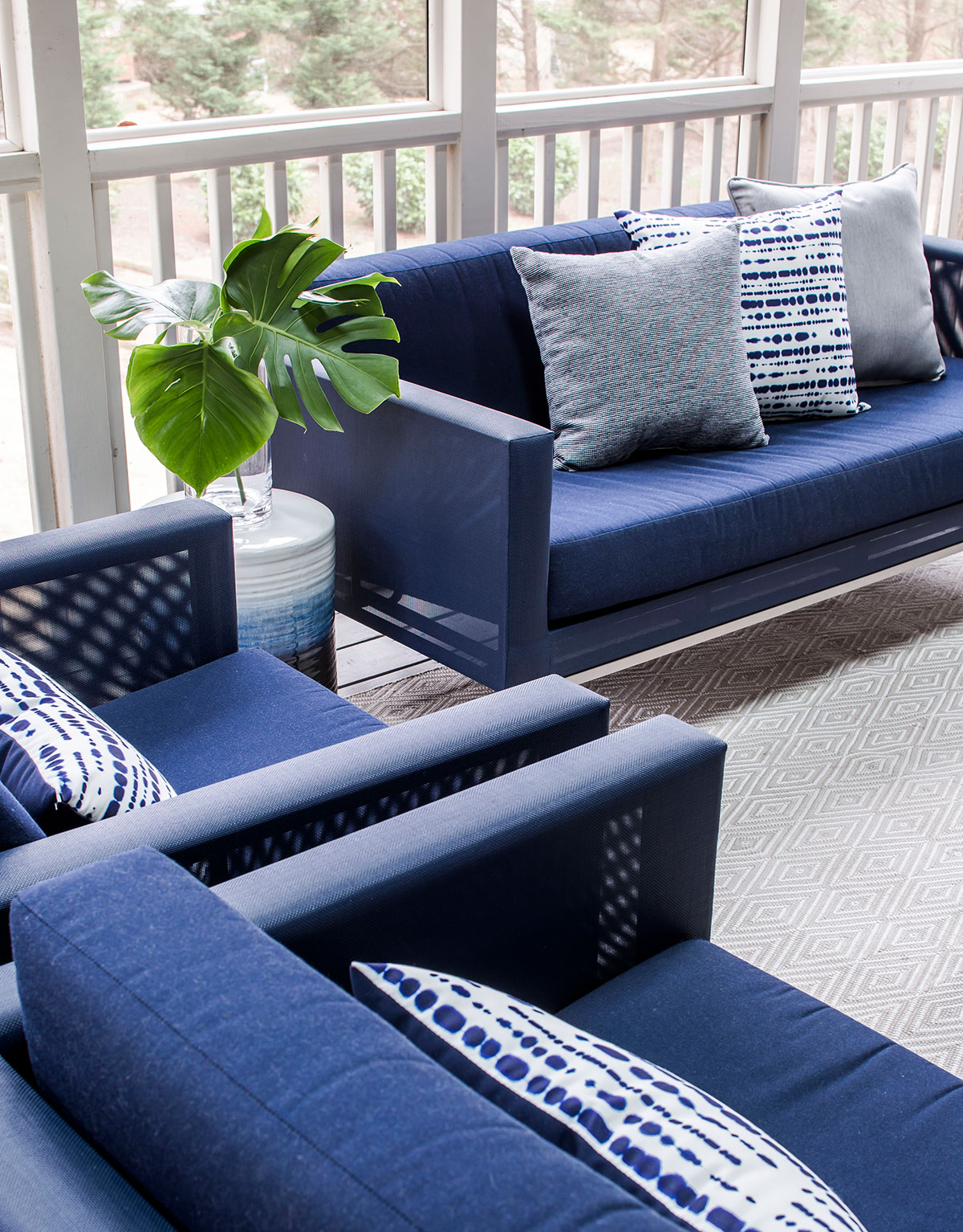 Screened-in porch with contemporary navy outdoor furniture