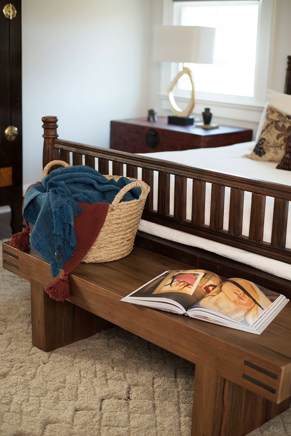 Wood bench at foot of bed in master bedroom