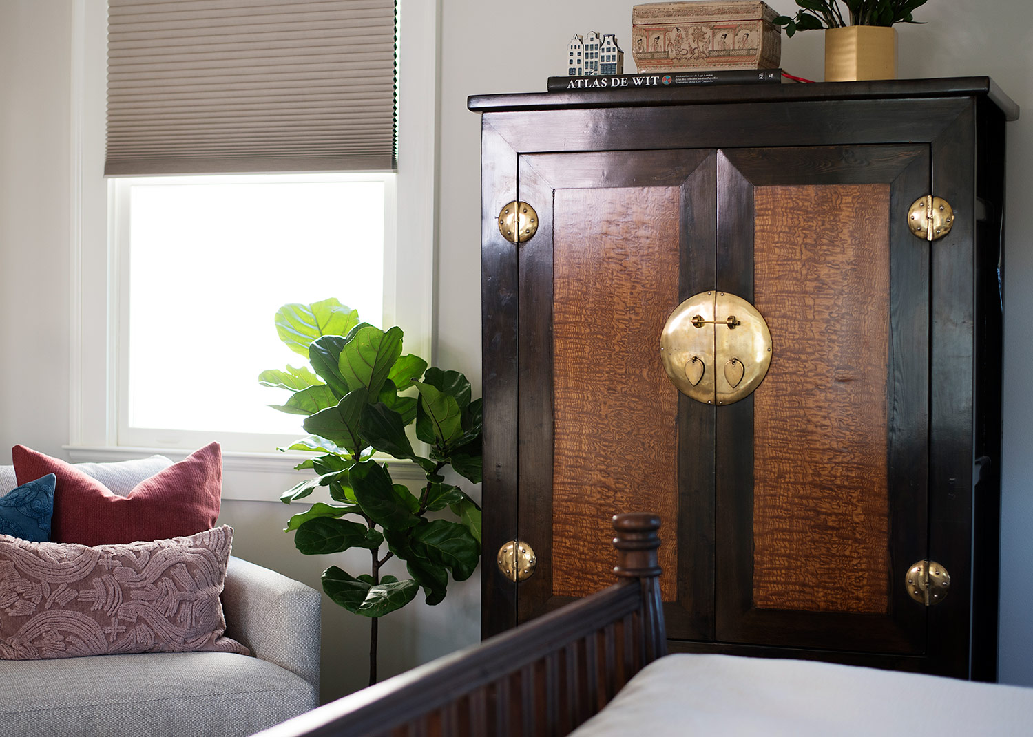 Antique wardrobe with brass hardware in master bedroom
