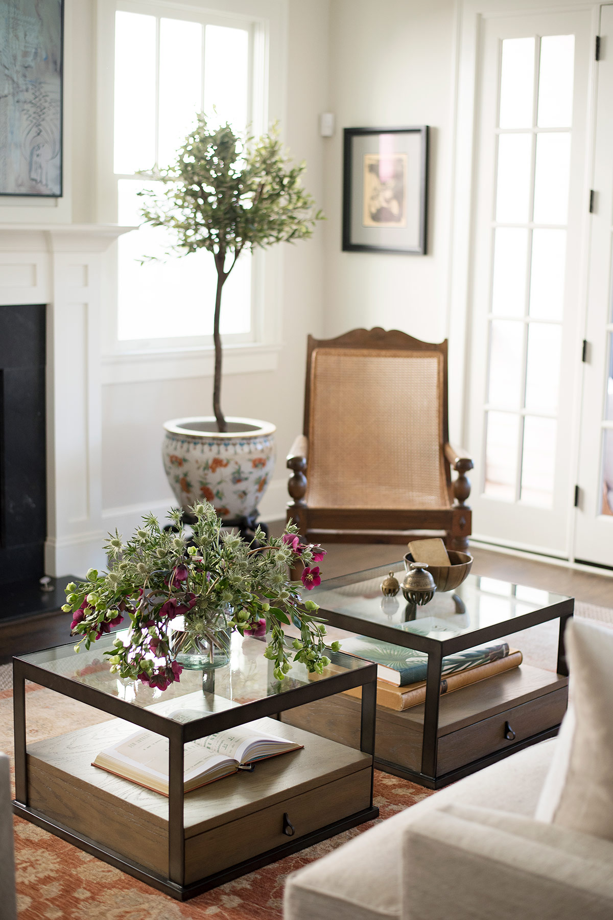 Matching glass coffee tables with books and flowers