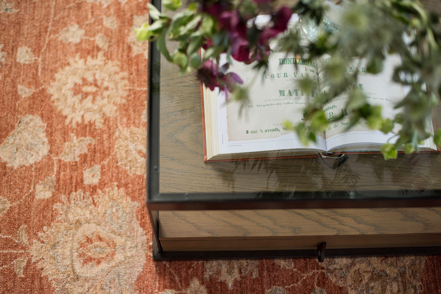 Orange floral rug and antique glass coffee table
