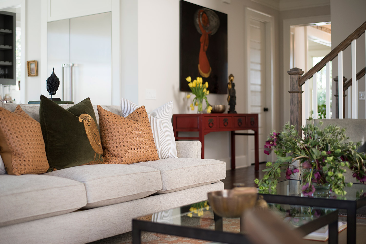Transitional living room with beige sofa and glass coffee tables