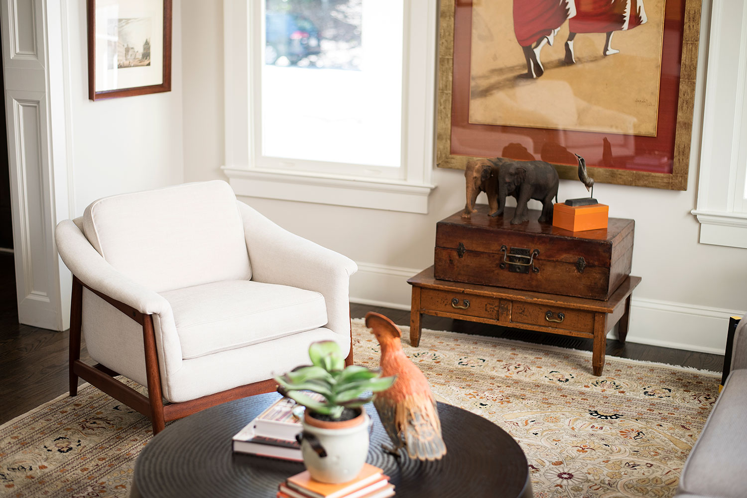 Transitional sitting room with ivory arm chair, beige area rug, and rich wood furniture