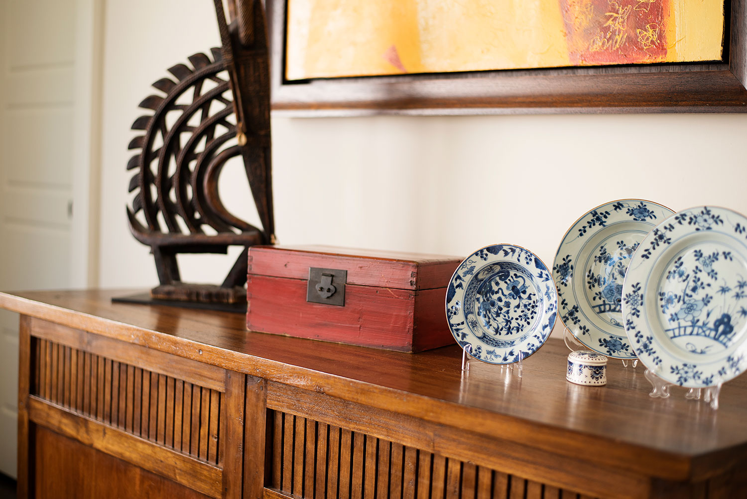 Wood sideboard displaying antelope sculpture and china plates