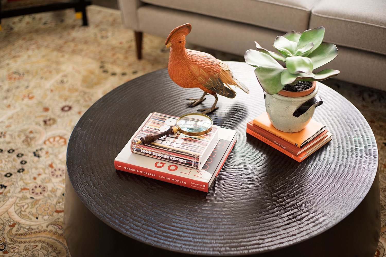 Round metal coffee table with books, potted plants and bird decor