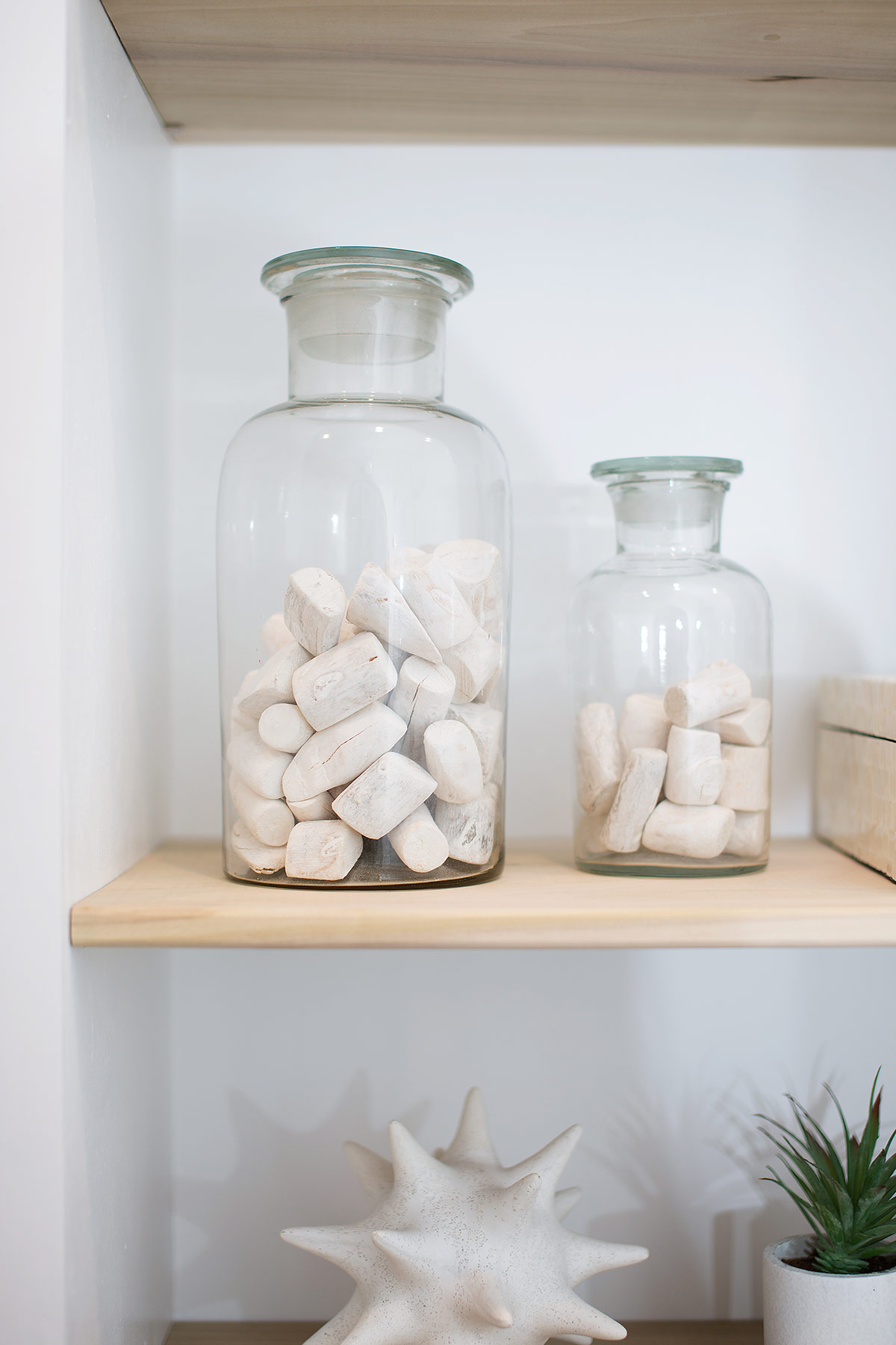 Glass bottles with coastal pebbles on built-in shelves in guest bathroom