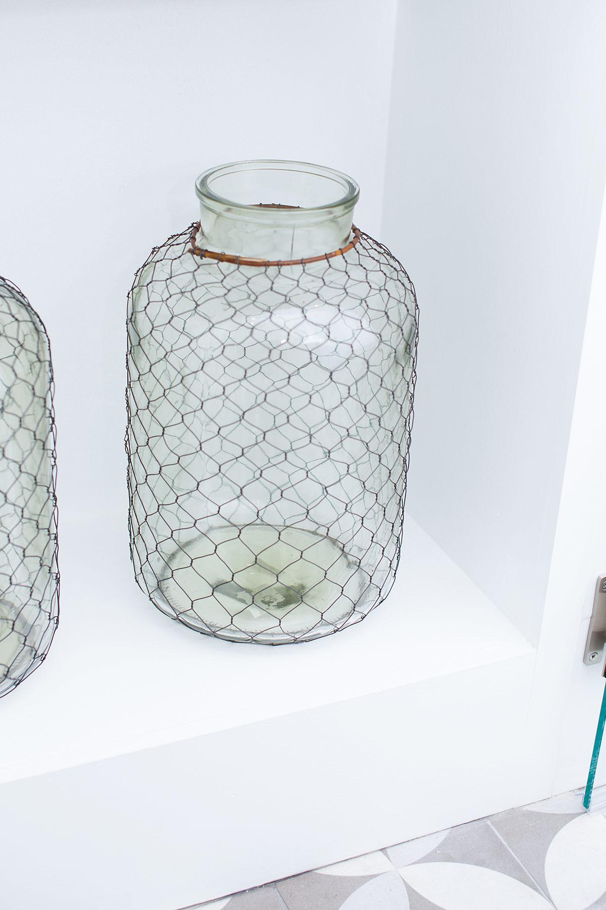Caged glass jars in coastal guest bathroom