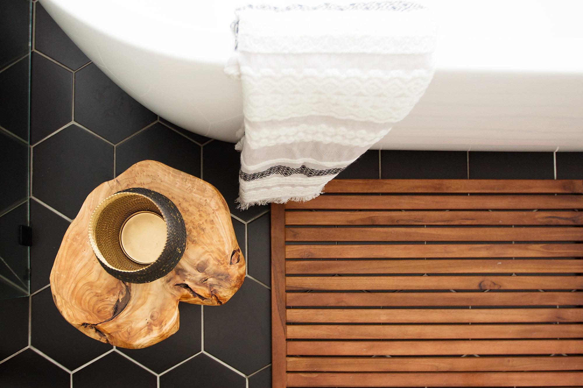 Black hex tiles and freestanding tub in midcentury modern master bathroom