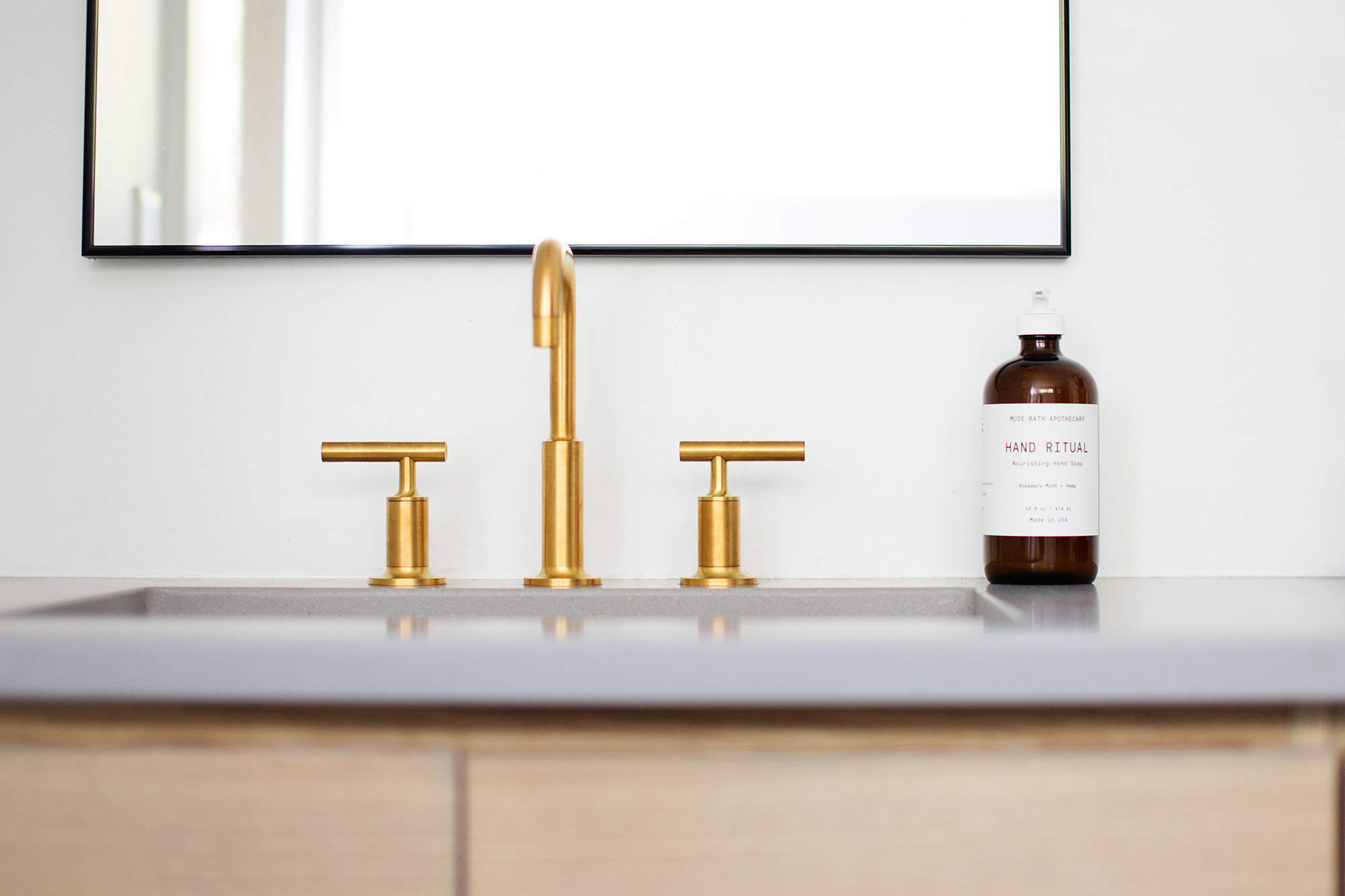 Sleek brushed brass faucet in midcentury modern master bathroom