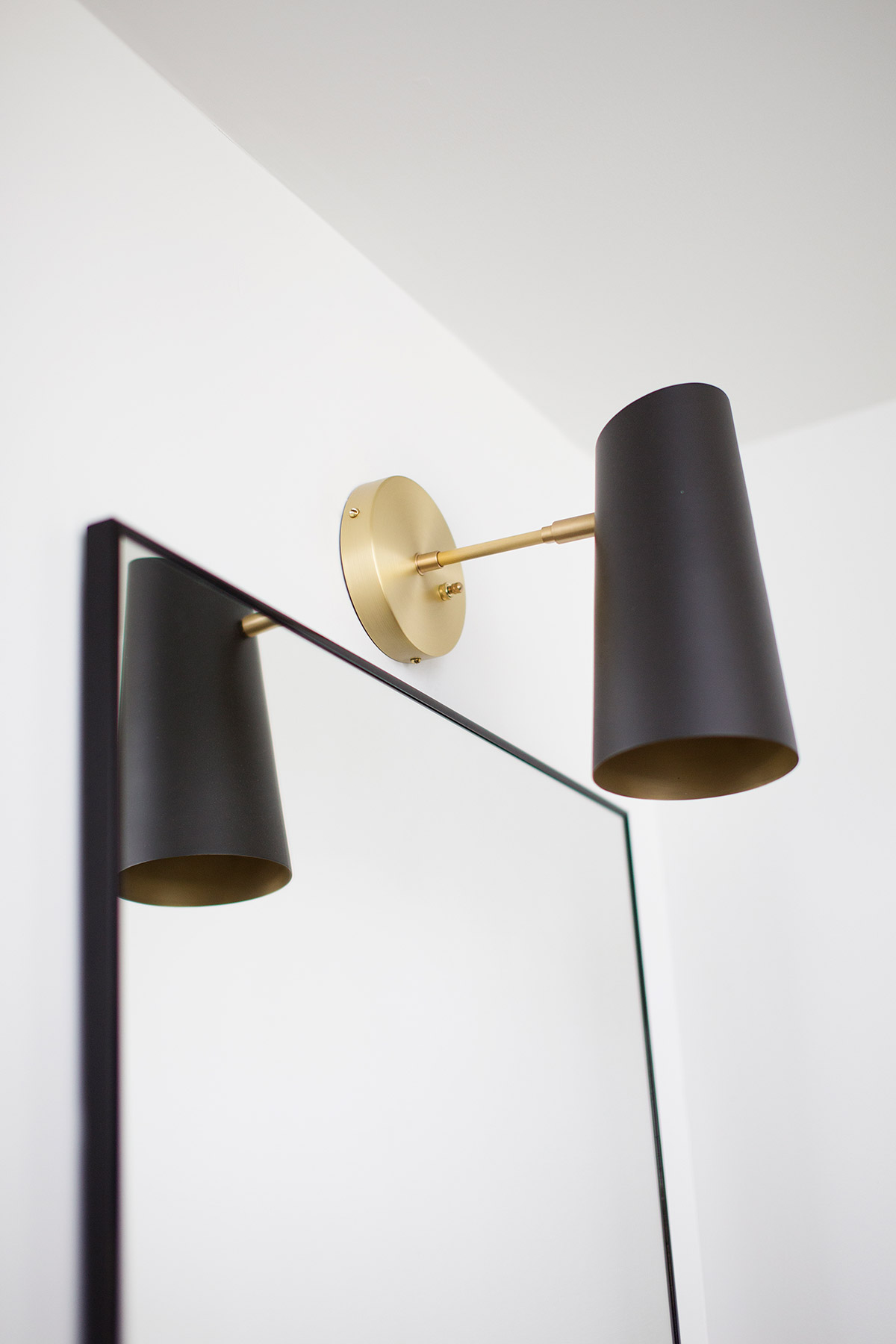 Midcentury modern brass sconce with black shade in master bathroom