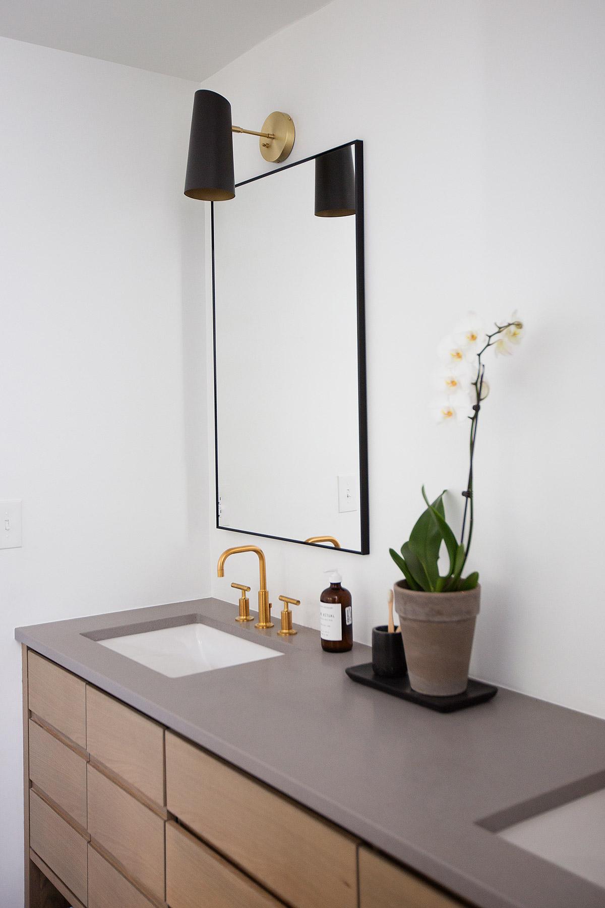 Built-in vanity with grey countertop in midcentury master bathroom