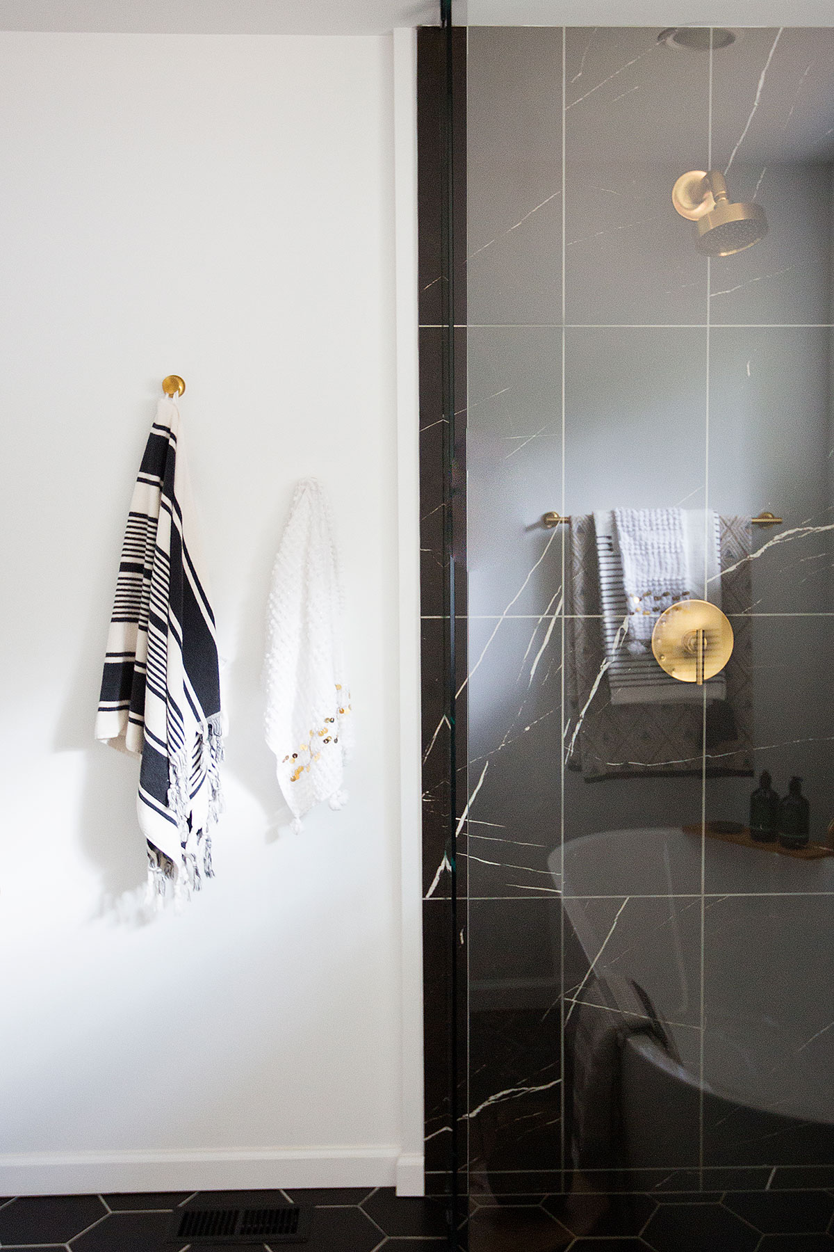 Walk-in shower with black marble tiles and brushed brass hardware in master bathroom
