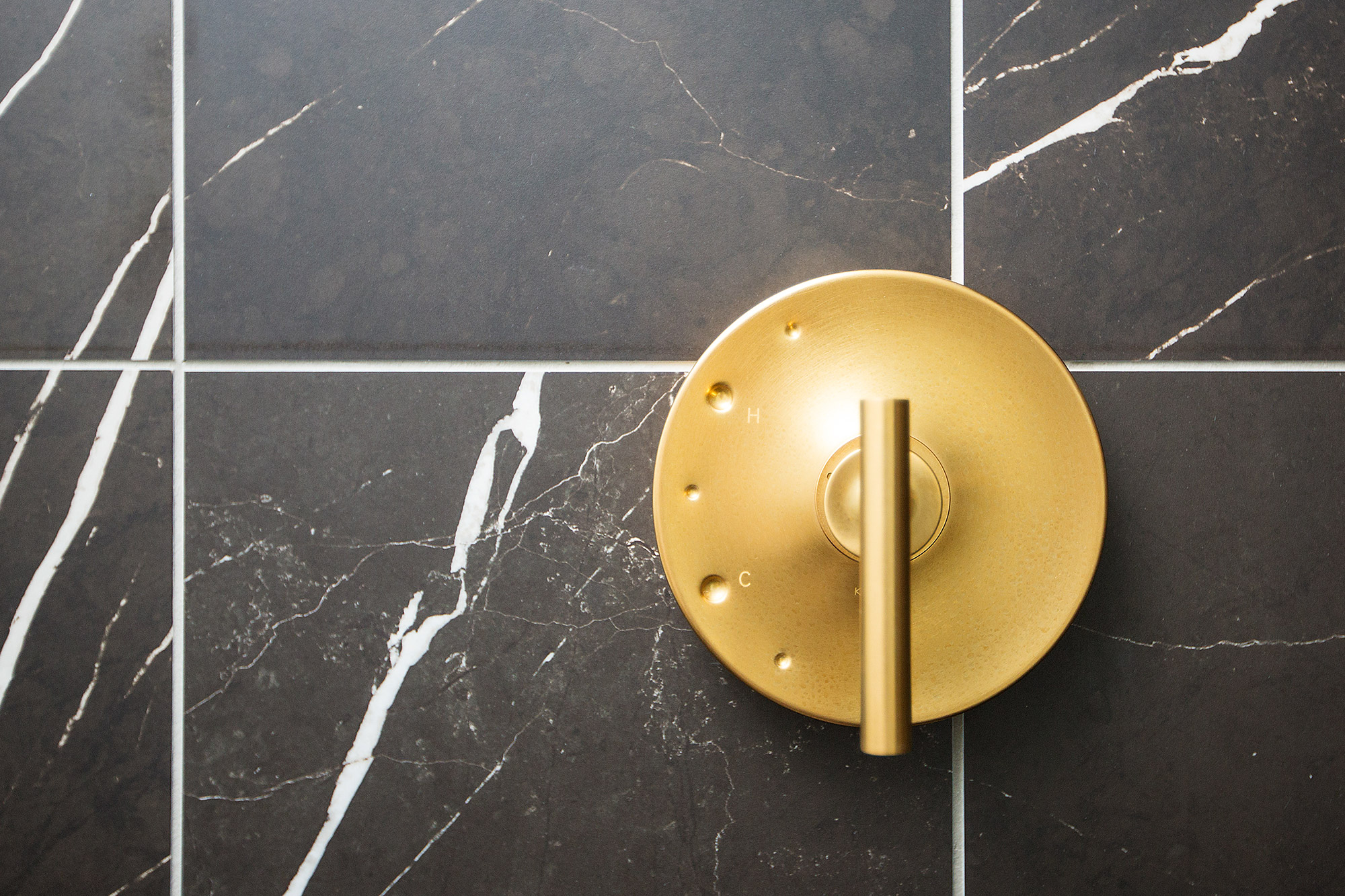 Black marble tiles and brushed brass plumbing in walk-in shower