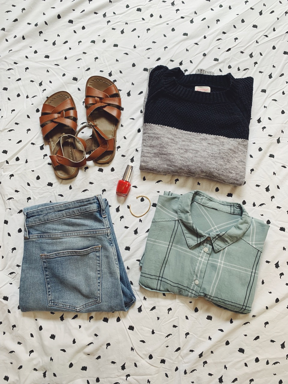 Clockwise from the top left: secondhand Saltwater sandals, secondhand linen–cotton Gorman sweater, organic cotton shirt, girlfriend jeans, O.P.I Unrepentantly Red nail polish and Odette NY arrow cuff.