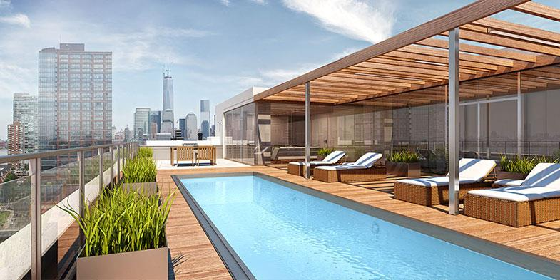 The building is of reinforced concrete construction, with projecting balconies at the rear. A penthouse level is set back from the front elevation. Amenities include a common rooftop terrace with a pool and an enclosed lounge.
