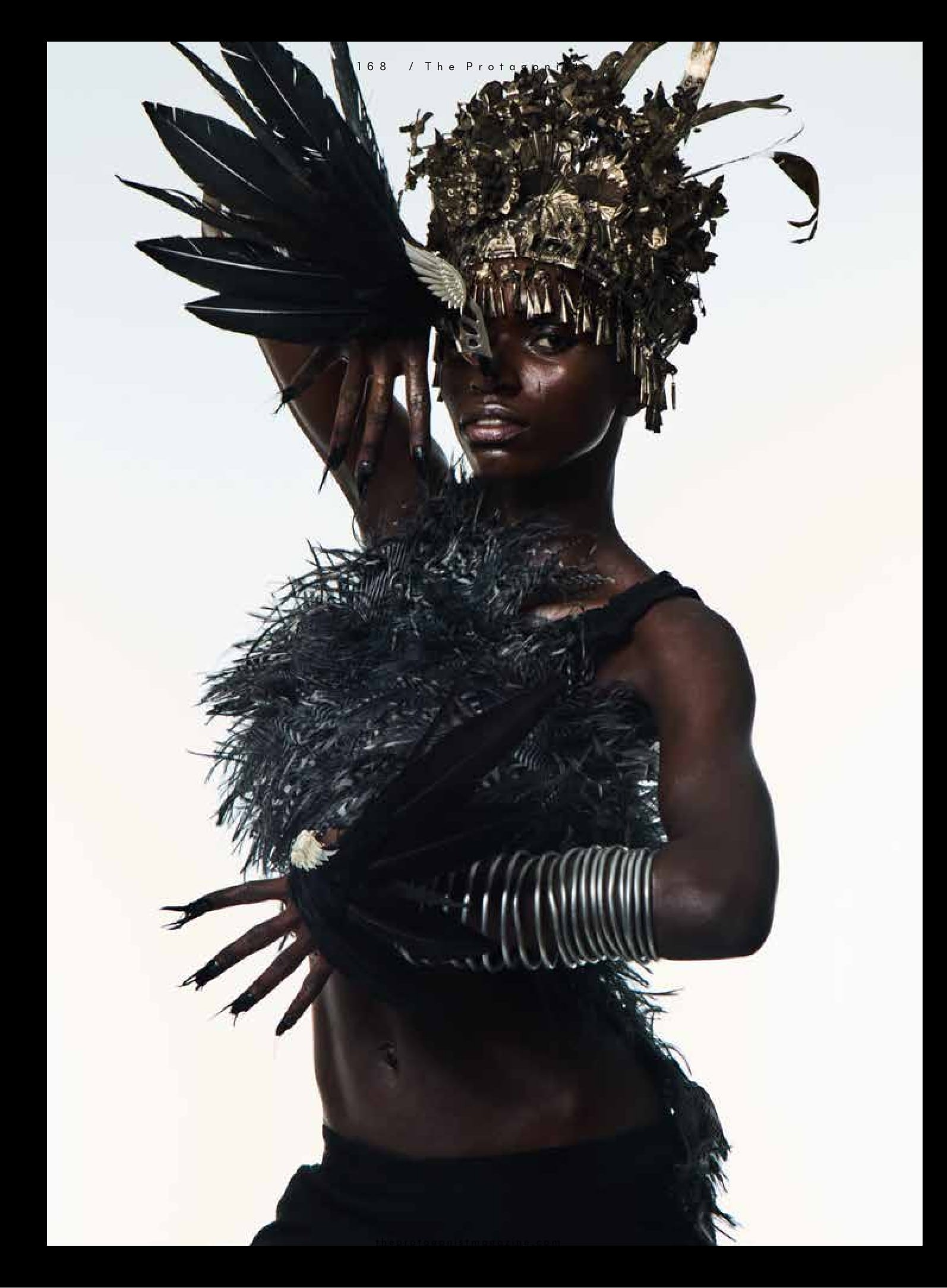 Black bumsters Alexander McQueen Nihilism collection SS1994. Metal headpiece and metal arm piece Pebble London. Feather brodice and feather top Carlos Miele. Black string vest Brixton Market. Victory feather winged thumb rings made to order Odette Jewellery.