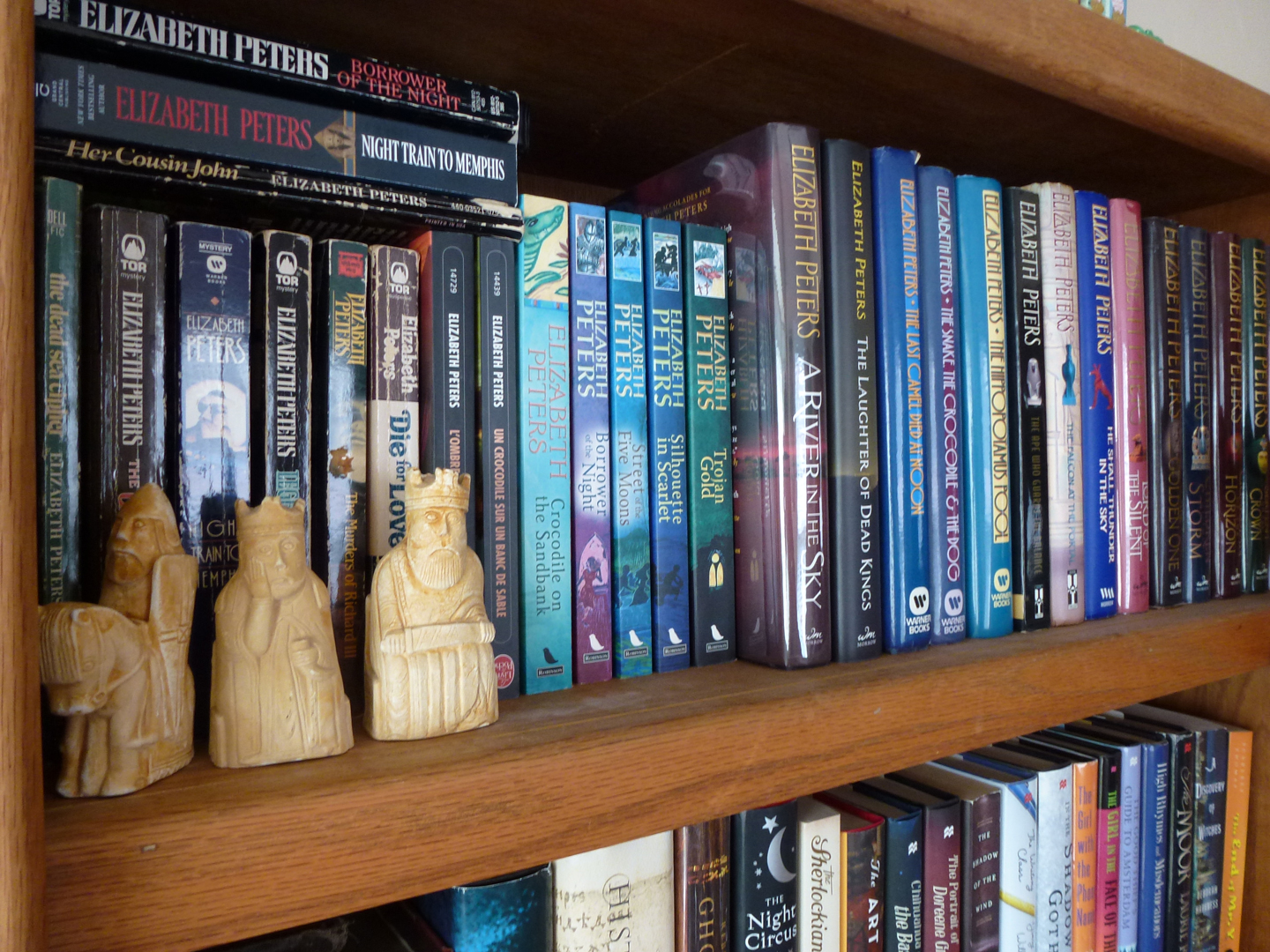 My bookshelf devoted to Elizabeth Peters novels. (And that's the Lewis Chessmen there on the shelf. These are ones I made out of plaster and painted as a fun project when I was a kid. See, I told you I couldn't escape my fate.)