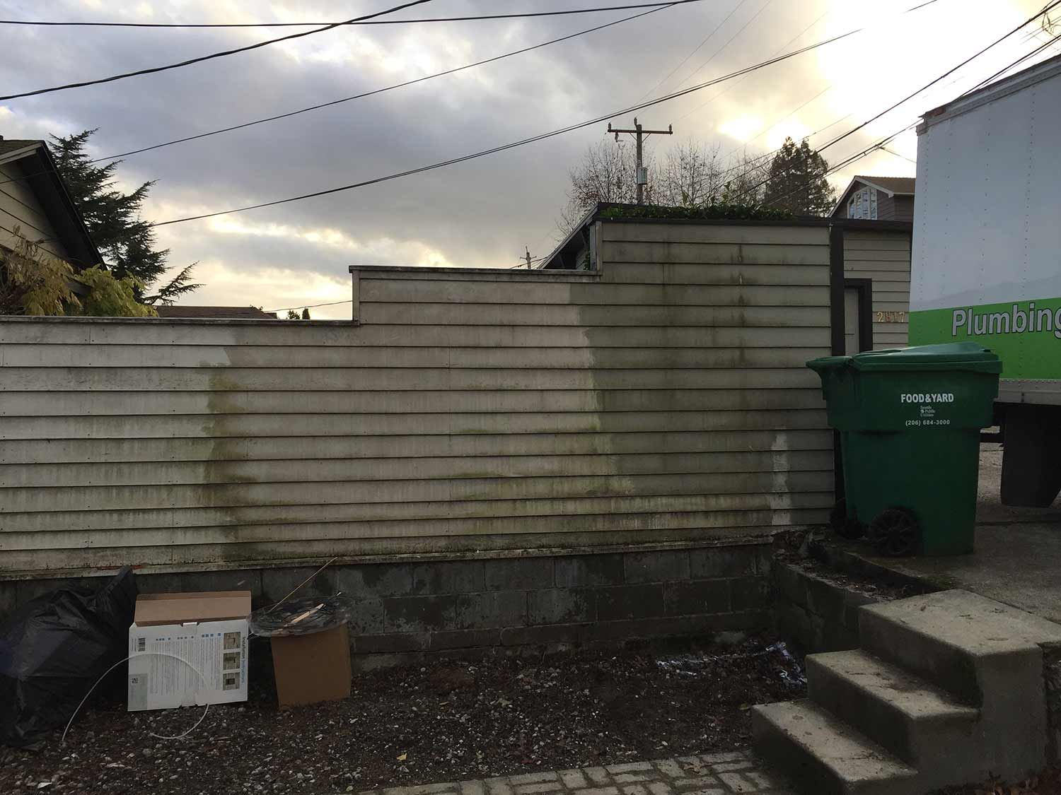 BEFORE:  BARE FENCE WITH UNPAINTED CONCRETE FOOTING