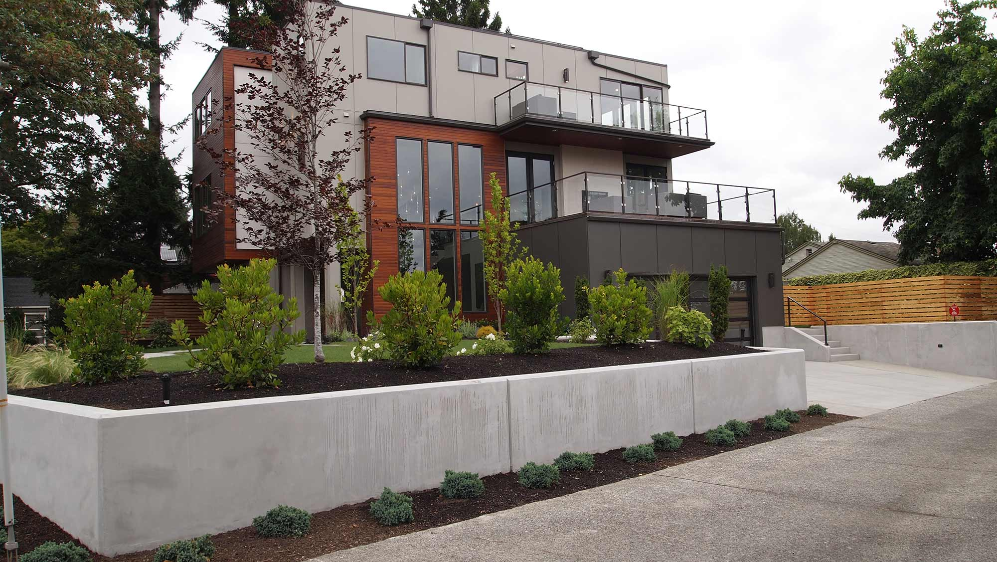 CONCRETE WALLS TO RETAIN THE GRADE AND BUFFERING EVERGREEN SHRUBS FOR PRIVACY